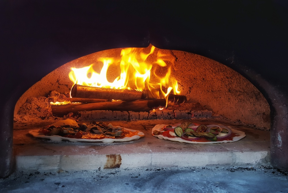 pizza cooking in a wood fired brick oven
